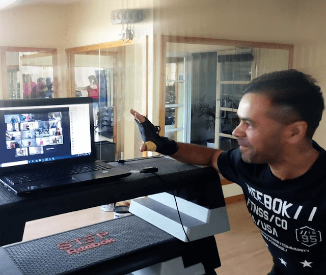 Instructor waving to participants during an online workout via Zoom